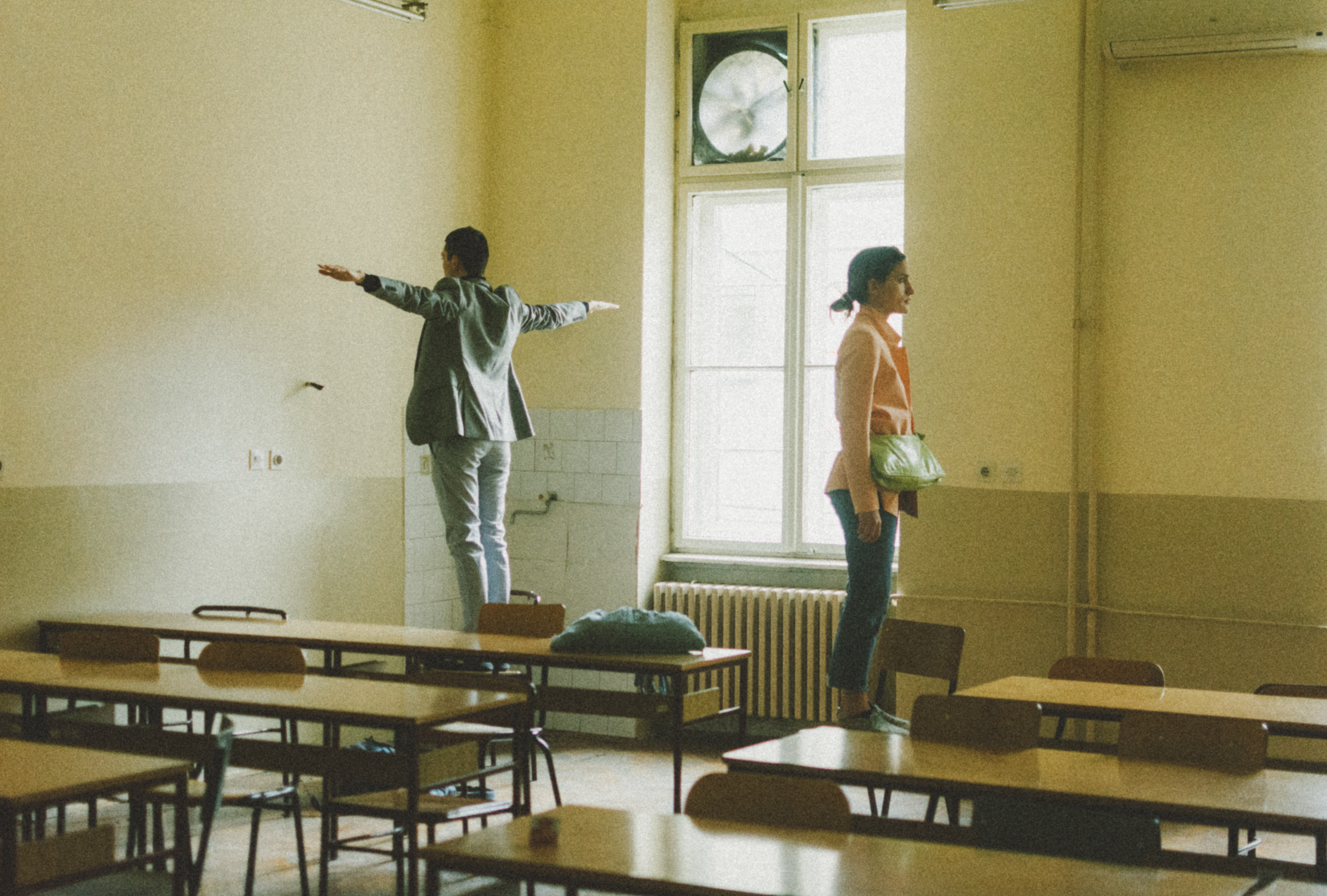 Photograph of two people in a classroom by https://unsplash.com/@ngelah